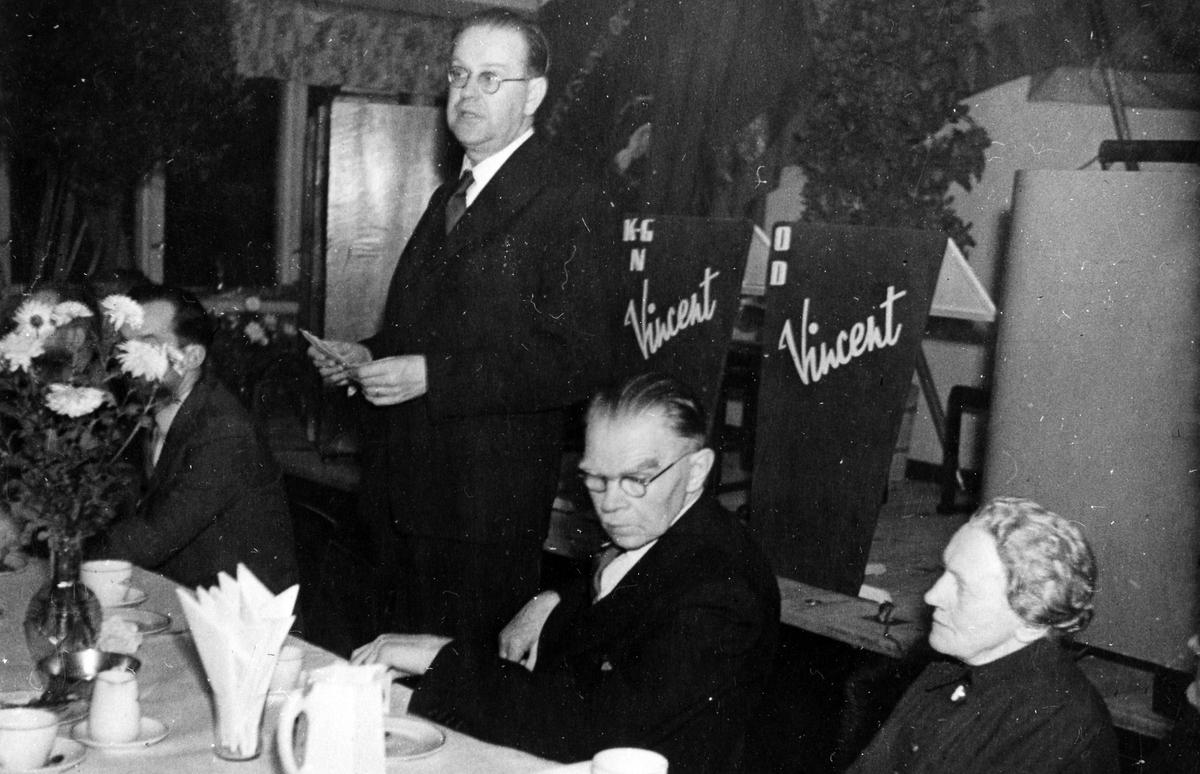 """Statsminister Tage Erlander på besök i Alingsås, en man och kvinna sitter till höger om honom. I bakgrunden syns en scen med några notställ och en dirigentpulpet samt en skylt med texten """"Vincent""""."""