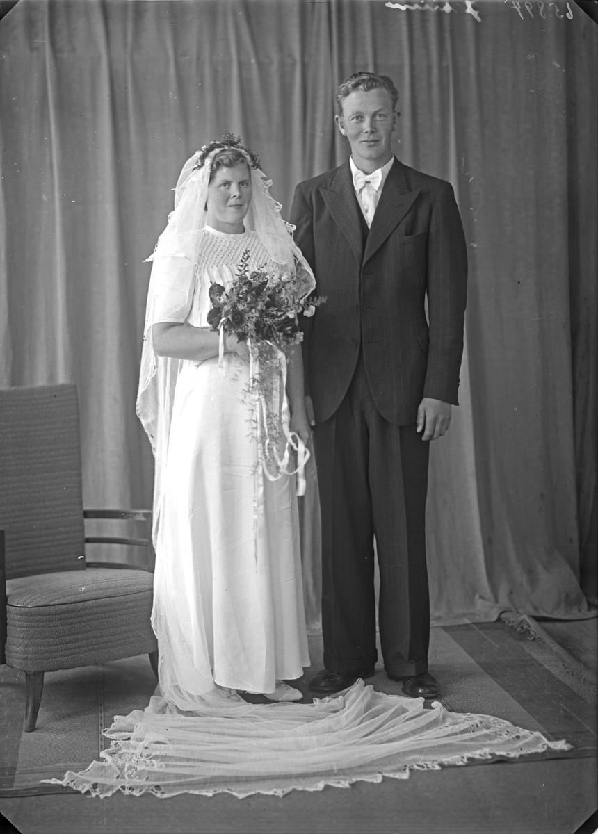 Portrett. Ung kvinne i hvit brudekjole med blomsterbukett og ung mann i mørk dress. Brudepar. Bestilt av Nils Nesse. Våga. Sveio