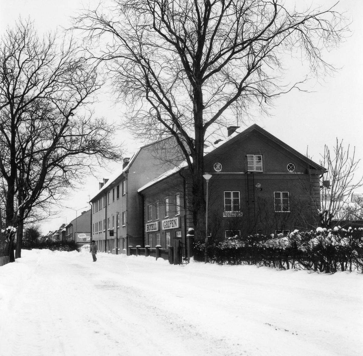 Vinterbild av en snötäckt Grindgata med Hotell Gripen i centrum på bilden och den fastighet som rivs mars 1979 för att ge plats åt trafiken på Vänersborgsvägen till vänster.
