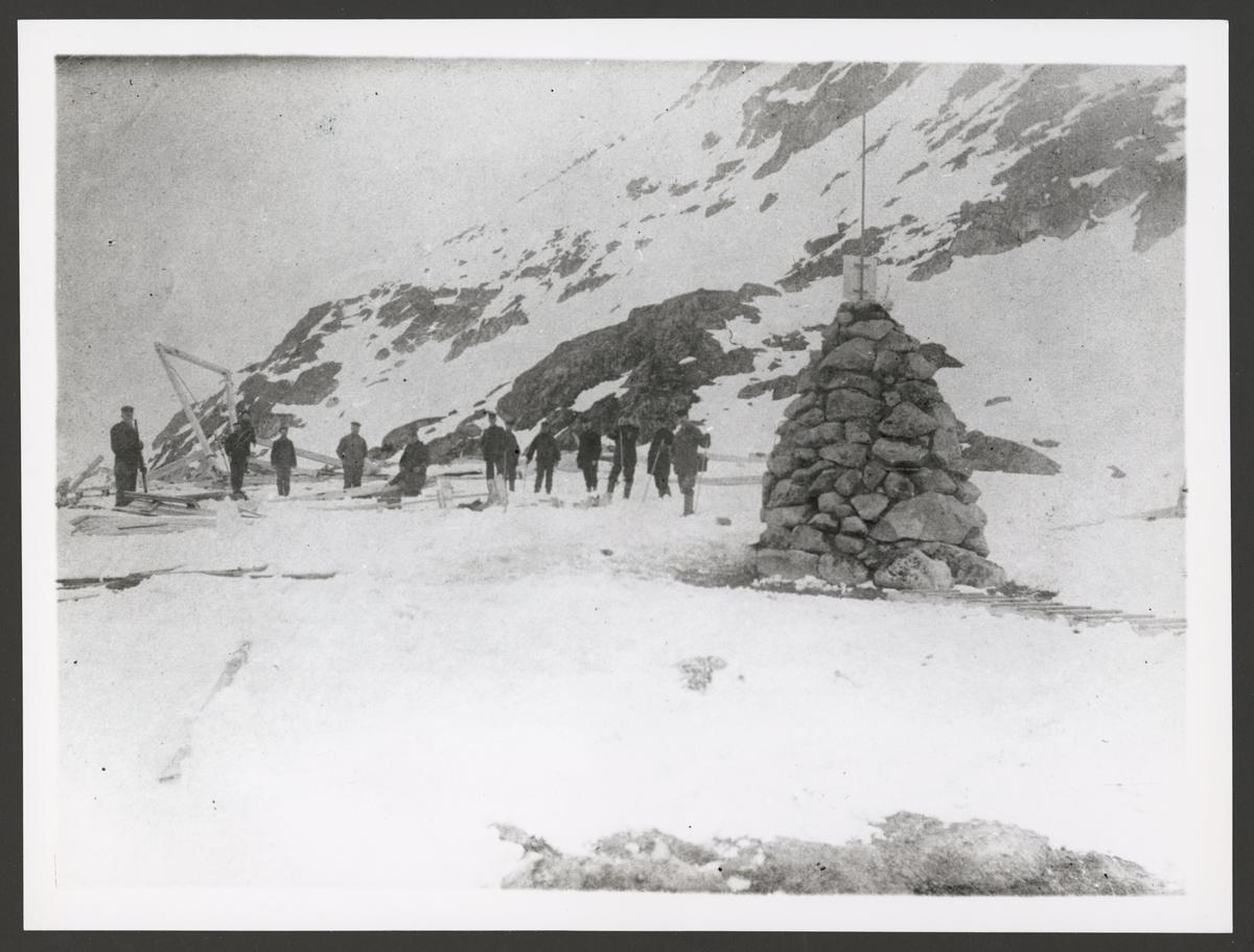 Bilden visar är en varde på Danskön. I bakgrunden syns resterna av Andrées ballonghus. En grupp män har tagit uppställning vis husresterna och tittar mot fotografen som håller fast sceneriet.