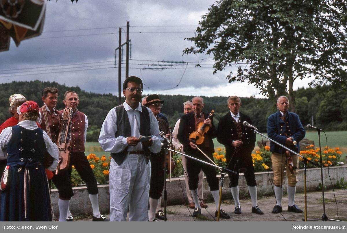 Staffan Bjerrhede presenterar Hällesåkers spelmanslag på hembygdsgården i Långåker, Kållered, den 23/8 1986. D 8:15.