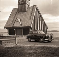 Bil foran en liten kirke.
