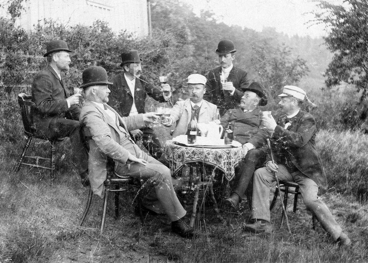 Midsommarfirande i Lindås 1893. Männen Artur Eneström, Alfred Larsson, C.A. Eriksson, Ade Sandberg, Albert Andersson, Petter Sandberg och Lionel Eneström sitter vid ett bord och dricker.