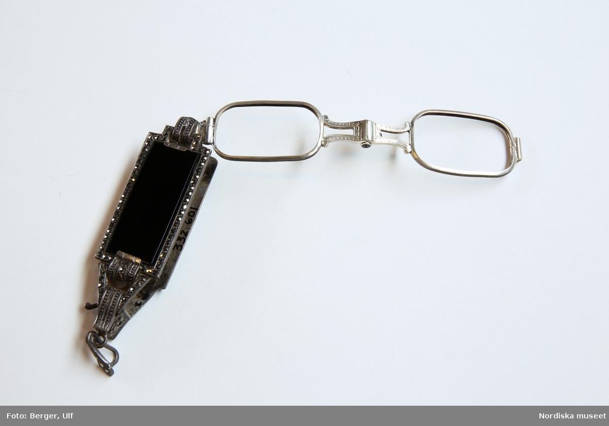 En springlornjett i silver med en svart rektangulär ruta, troligen av glas, på framsidan och ett blommigt mönster på baksidan. Strassdetaljer runt kanterna på framsidan. Fast hängögla fäst nedtill, i denna en ring för kedja eller band. Inga glas i de fällbara glasögon. /Petrine Knight, 2015-08-31