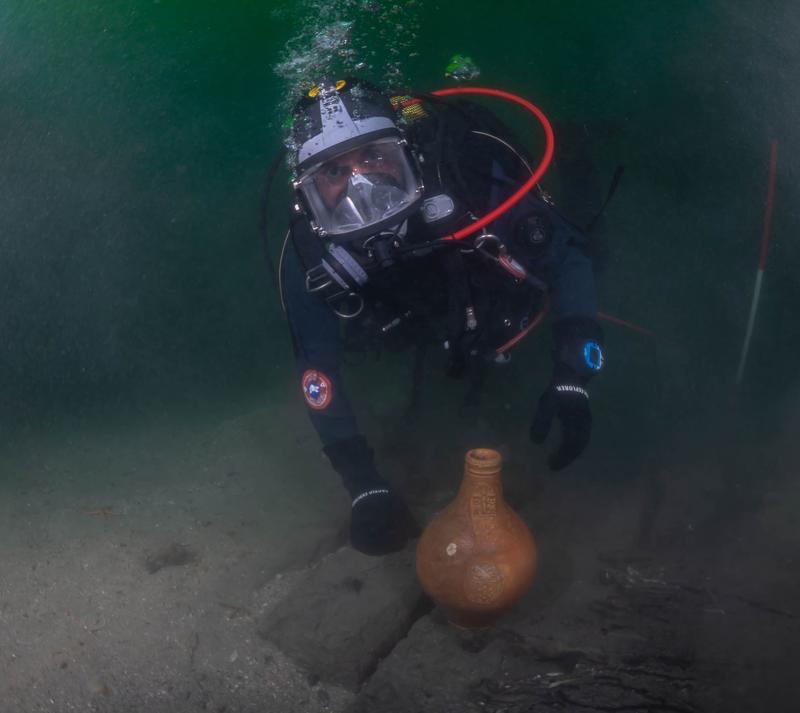 Dykkende arkeolog viser frem bartmannskrukke funnet i vraket av det som antas å være Pelikanen.
