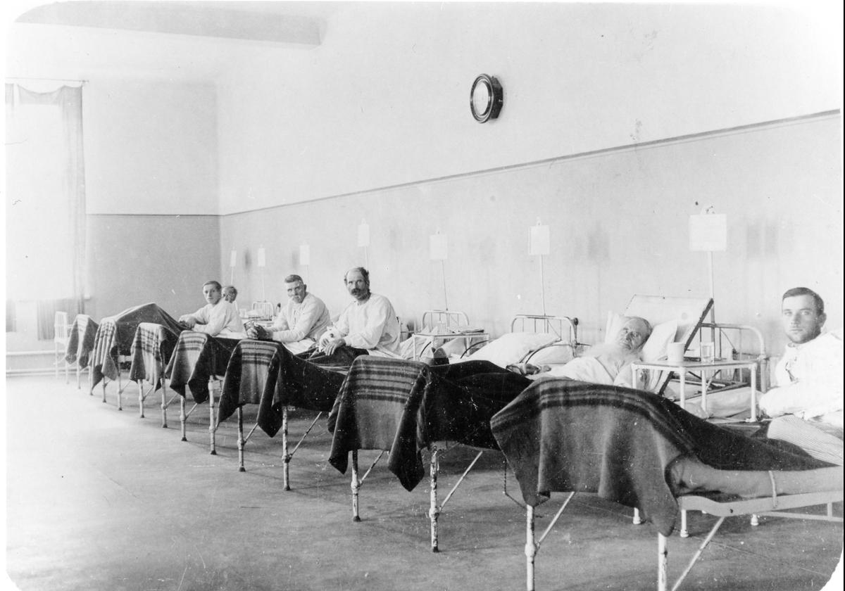 Bild tagen inifrån en vårdsal på Alingsås Lasarett med 8 patientsängar och 6 manliga patienter.