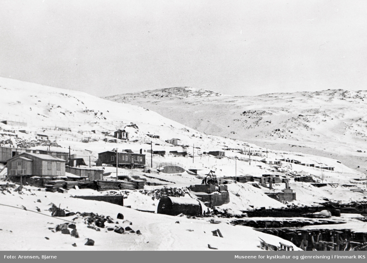 Honningsvåg. Gjenreisningen. Brakker, i bakgrunnen Elvedalen. I midten rester av smed Evensens forstøtningsmur i Storgata. Vinter 1946.