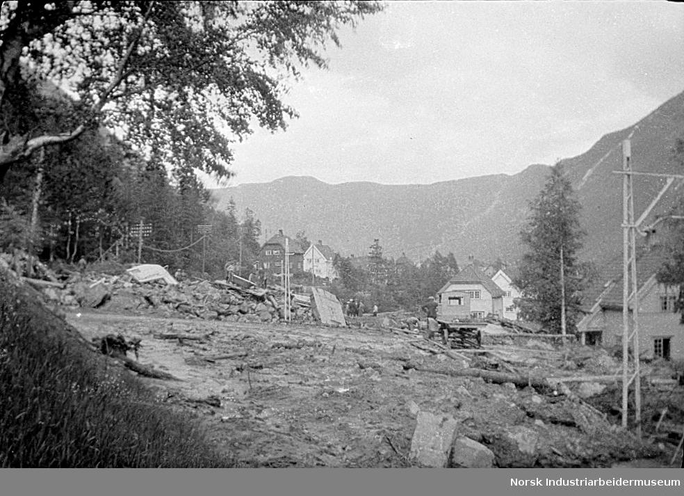 Storflommen og jordskred sommeren 1927. Hus ødelagt av skred. Kraftlinjer i bakgrunnen
