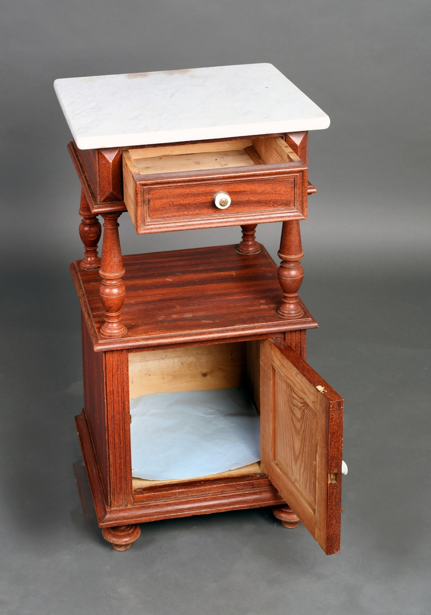 Nattbord i tre med marmorplate. Med fire dreide føtter. Nattbordene har ett skap nederst, og èn skuff på fire dreide profilerte søyler. Åpen hylle mellom skuff og skap. Marmorplaten er montert over skuffen.
