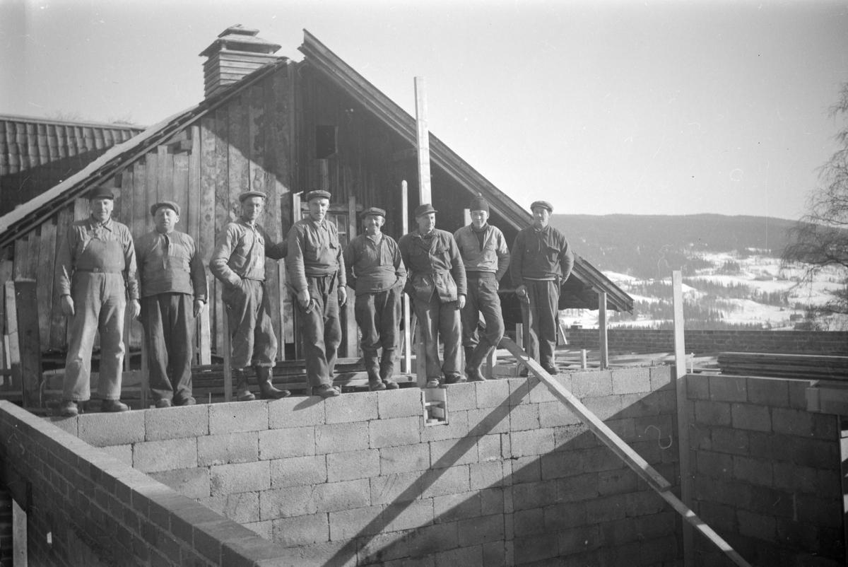 Arbeidslag på åtte mann i arbeid med tilbygg til større bygning