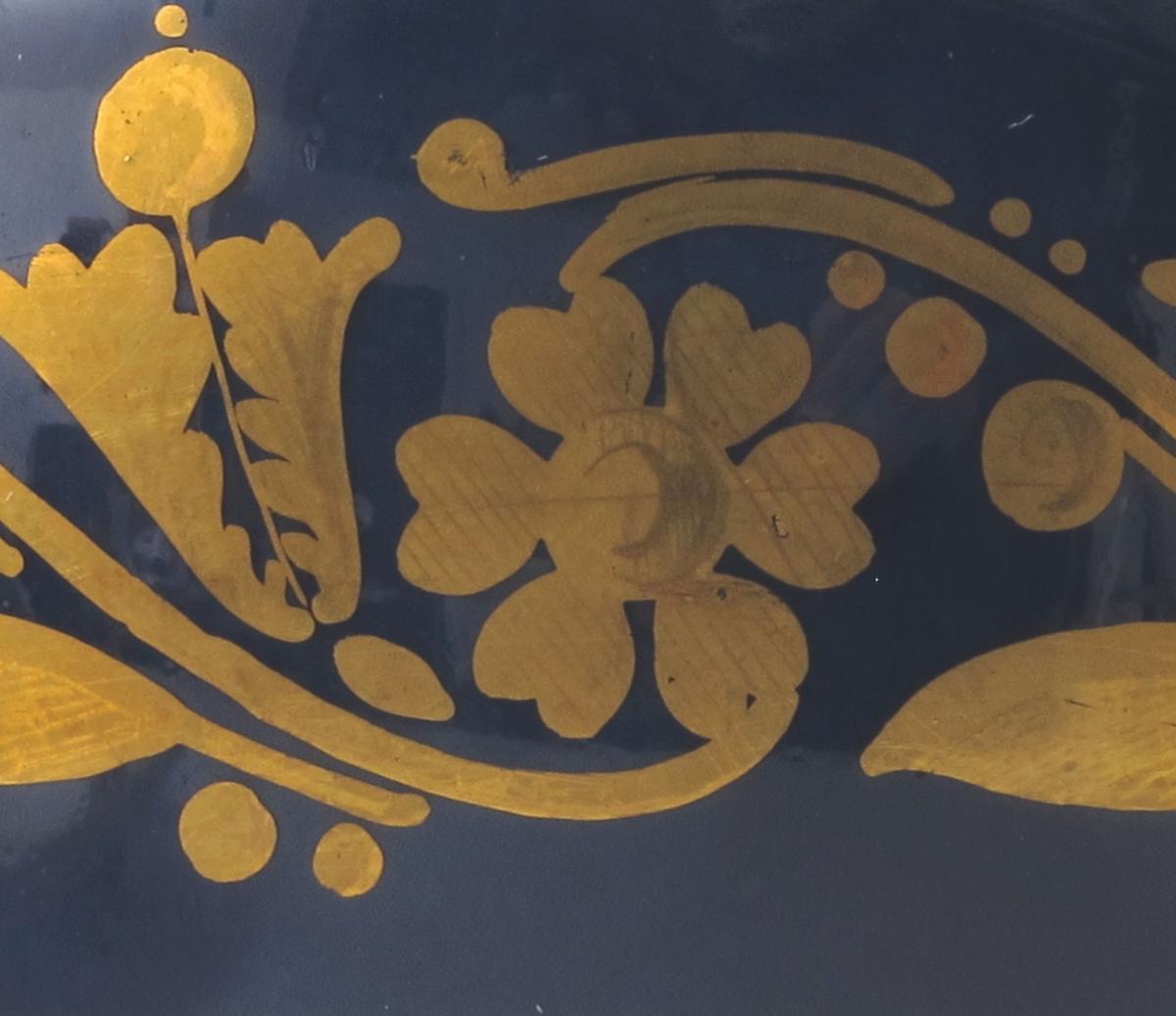 """A) Kopp: Empirefor. Høy, smalner av ned mot hvelvet fot. Innsvunget øverst mot utsvunget. munning. Forgylling fortsetter innvendig langt ned i koppen. På yttersiden forgyllet bord av blad og blomster på dypblå bunn. Lenger nede enda en forgyllet bord. Høy hank.   B) Skål: Flatt hvitt speil med to forgylte ringer i sentrum. Blå sider med forgyllet dekor og kant.    Malt under bunnen på kopp og skål: Grønn """"hval""""."""
