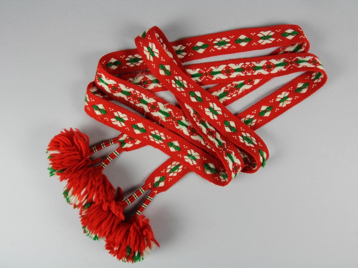 Mönstervävt band med botten av rött ullgarn och mönster i grönt ullgarn och vitt ullgarn. I ändarna är äfsingarna delade i två grupper som lindats tätt med garn och varje del avslutas med en tofs i bandets färger.