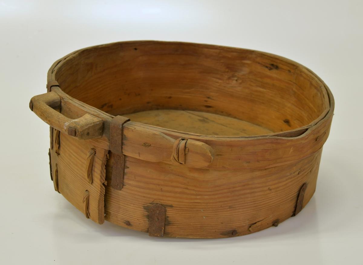 Handtag av trä i ena sidan, upphängningsring av järn i den andra sidan. Fästen av järn som håller fast botten.