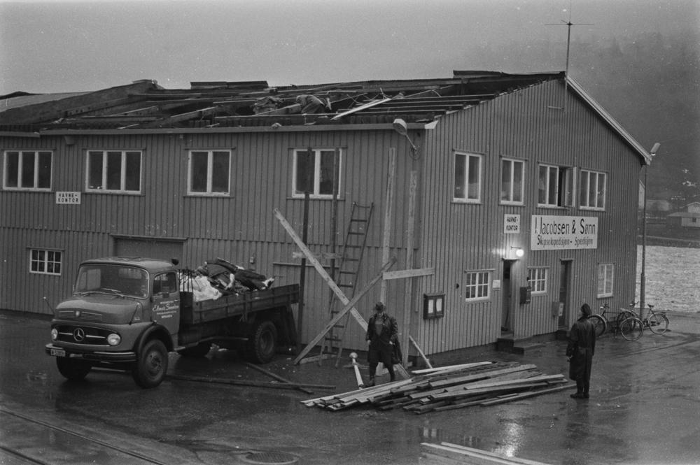 Skader etter uværet 10.Januar 1971. Skader på taket til J.Jacobsen & Sønn/Havnekontoret. Oppryddingsarbeid.
