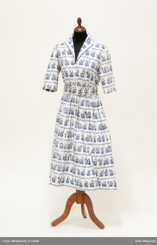 A: Sommerkjole i hvitt med gråblått mønster B: Belte  Dekor: trykket mønster med kinesiske figurer og border Størrelse: 42  Prinsesse Astrid hadde maken