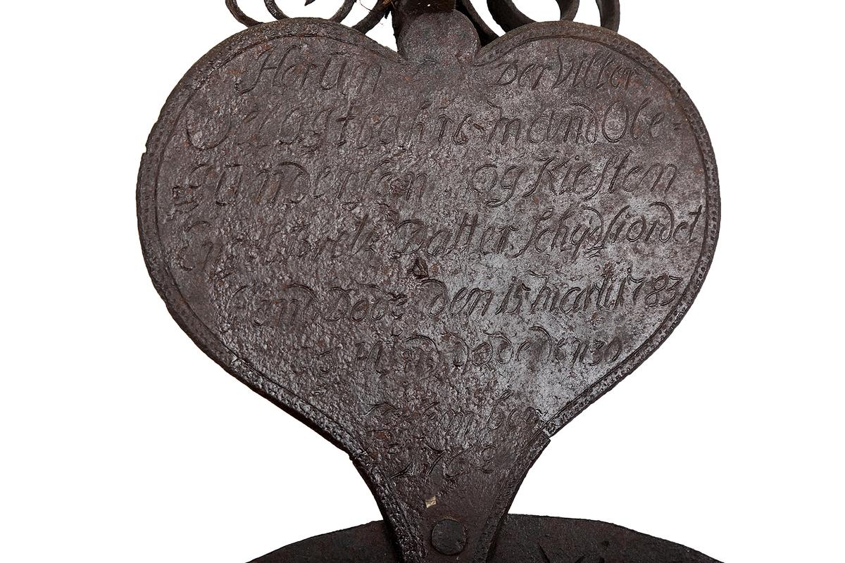 Høyt og smalt gravkors av smijern. En snodd jernstang og to sidespir danner et kors. To mindre spir over disse. to hjerter og en dobbelt sirkel mellom hjertene. Øverst en bladformet liten jernplate med utskåret kors. Dekorelementer av bøyde jernbånd på spir og stammen.