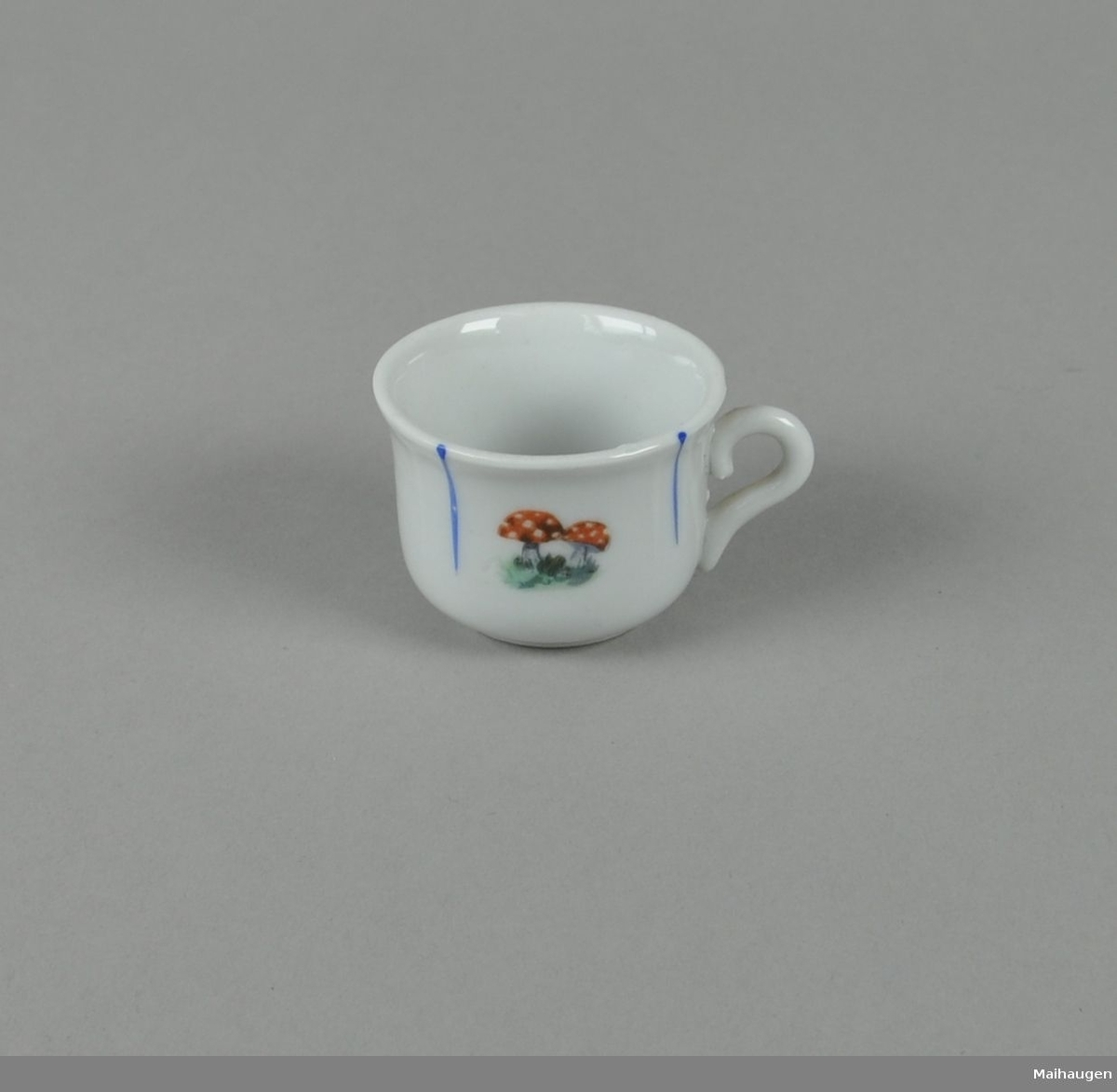 Hvit kopp av glassert keramikk, med malt dekor av nedovergående blå striper og fluesopp i midten.