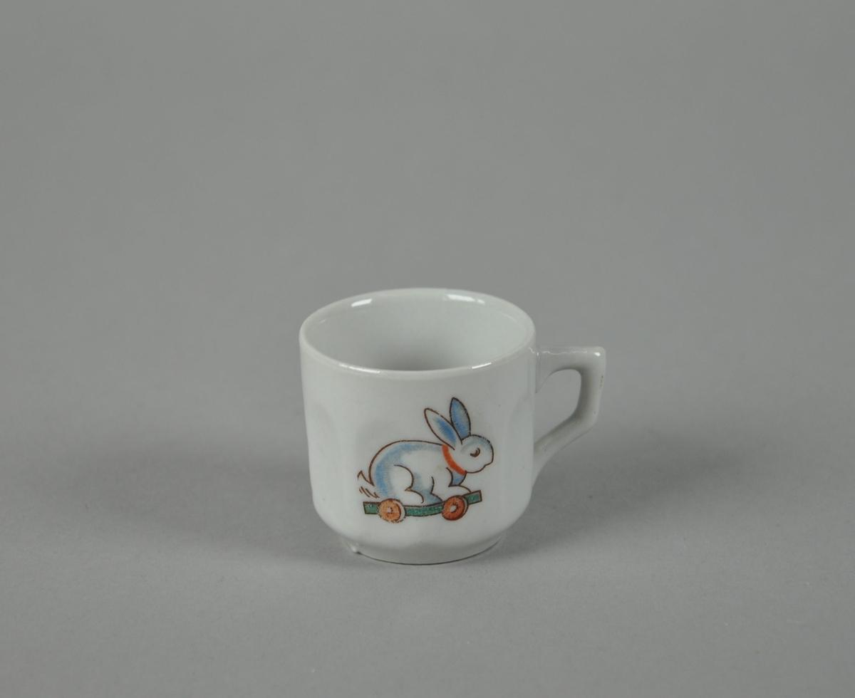 Kopp av glassert keramikk, med fasettert form. Hvit farge, med farget motiv av harer på kjelke med hjul.
