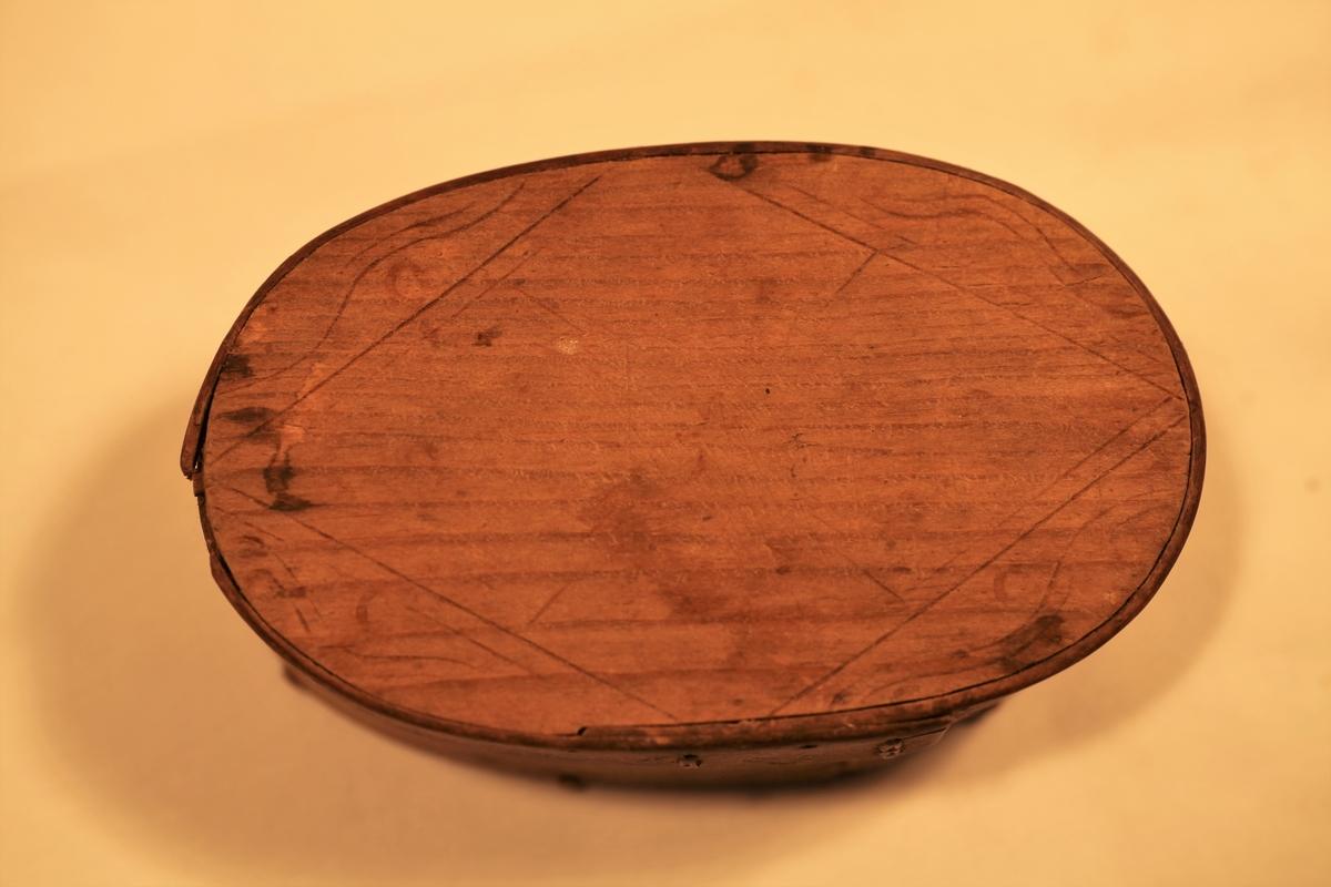 Avlang smørøskje der bunnen er laget av ett trestykke, og sidene er laget av tjukke høvelspon. Sponen er skjøtt med tæger, og den er festet til bunn og toppstykke med trenagler. På lokket er det enkel sviornamentikk.
