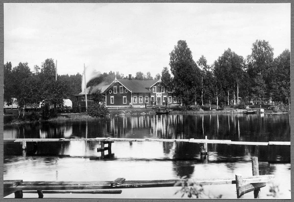 """Strömsdal station sett från Hyltsjön med Sävsnäs Järnväg, SVJ lok 5 """"Strömsdal"""" i bakgrunden."""