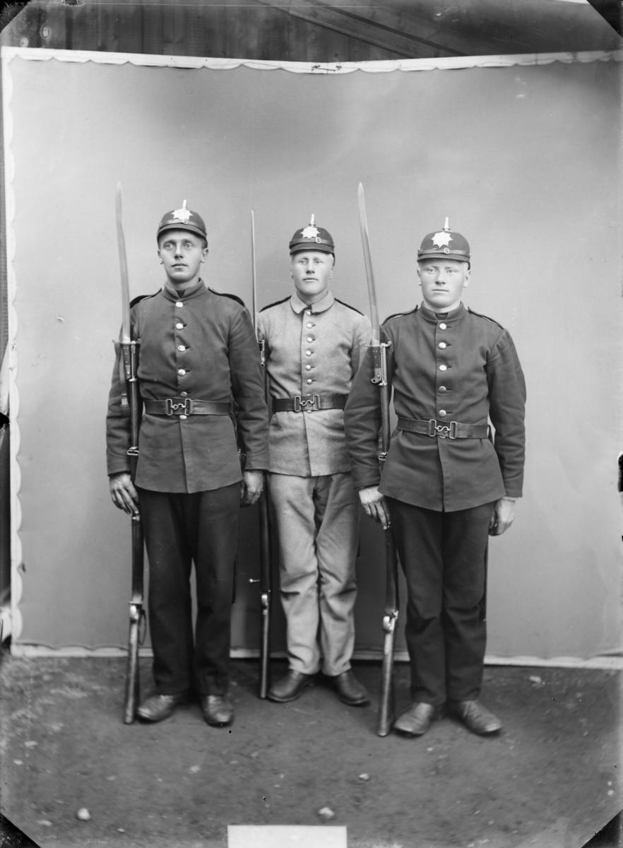 3 soldater fra Bjorli/Lesjaskog med gevær, bajonett og hjelm model 1891. Den lyse uniformen er infateriets våpenfrakk modell 1888. De mørke uniformene er antatt modell 1894 for sanitetskorpset. Antatt sted Jørstadmoen, Fåberg.