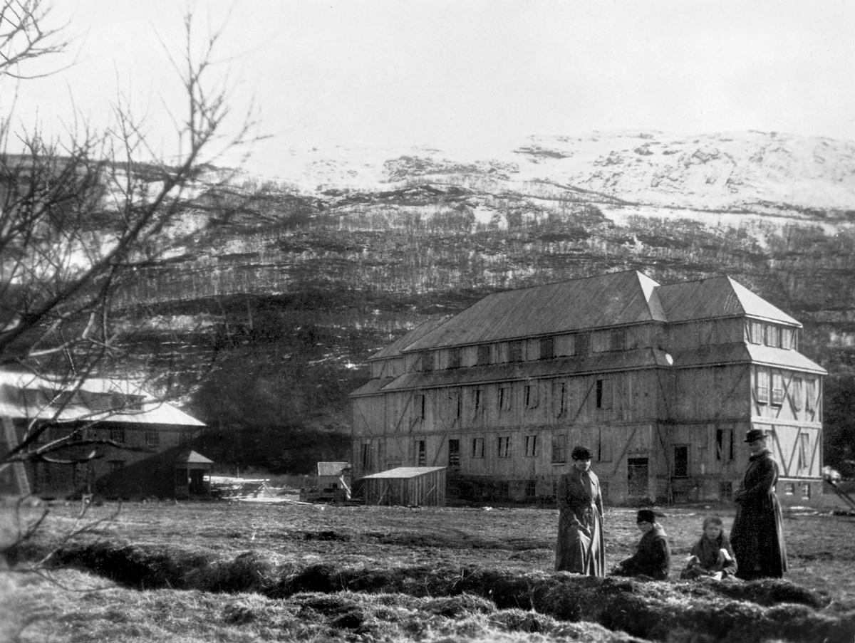 Lærerskolen på Nesna under bygging. Tre kvinner i kåper og hatter og ei jente i forkant.