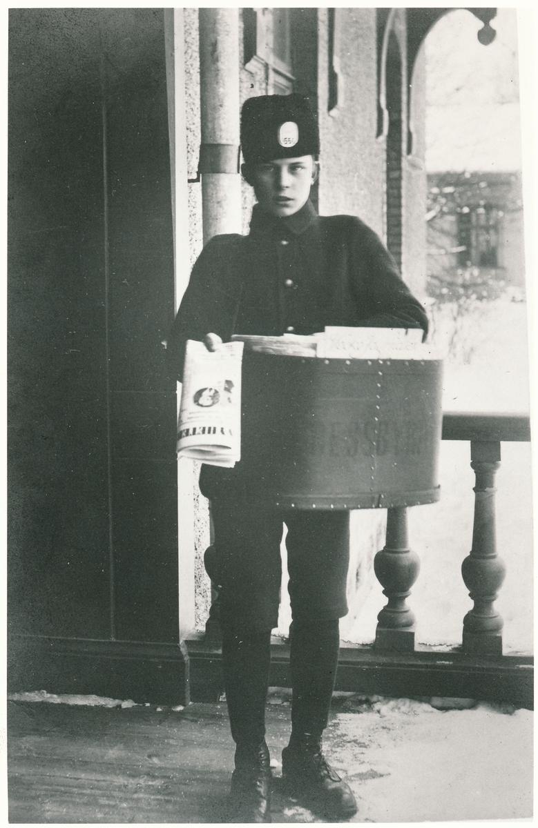 Fotot taget på Sandvikens hotell. Ernst Arvid Larsson, Lasse, född 1900-08-31 i Vrenninge eller Fläckebo i Västmanland, han  avled 1980-07-09. Fadern var nattvakt på GDJ, Gävle - Dala Järnväg och ansåg att enda möjligheten för den 14-årige sonen Ernst Arvid att komma in vid järnvägen var att börja som tidningspojke. Här syns han i uniform och Pressbyrås väskan med troligen Dagens Nyheter i handen, Han hade mössa med nr 556 och snökängor på sig. Man lär ha sagt till pojke- kom in ska Du bli bjuden på något sedan togs kortet på verandan.