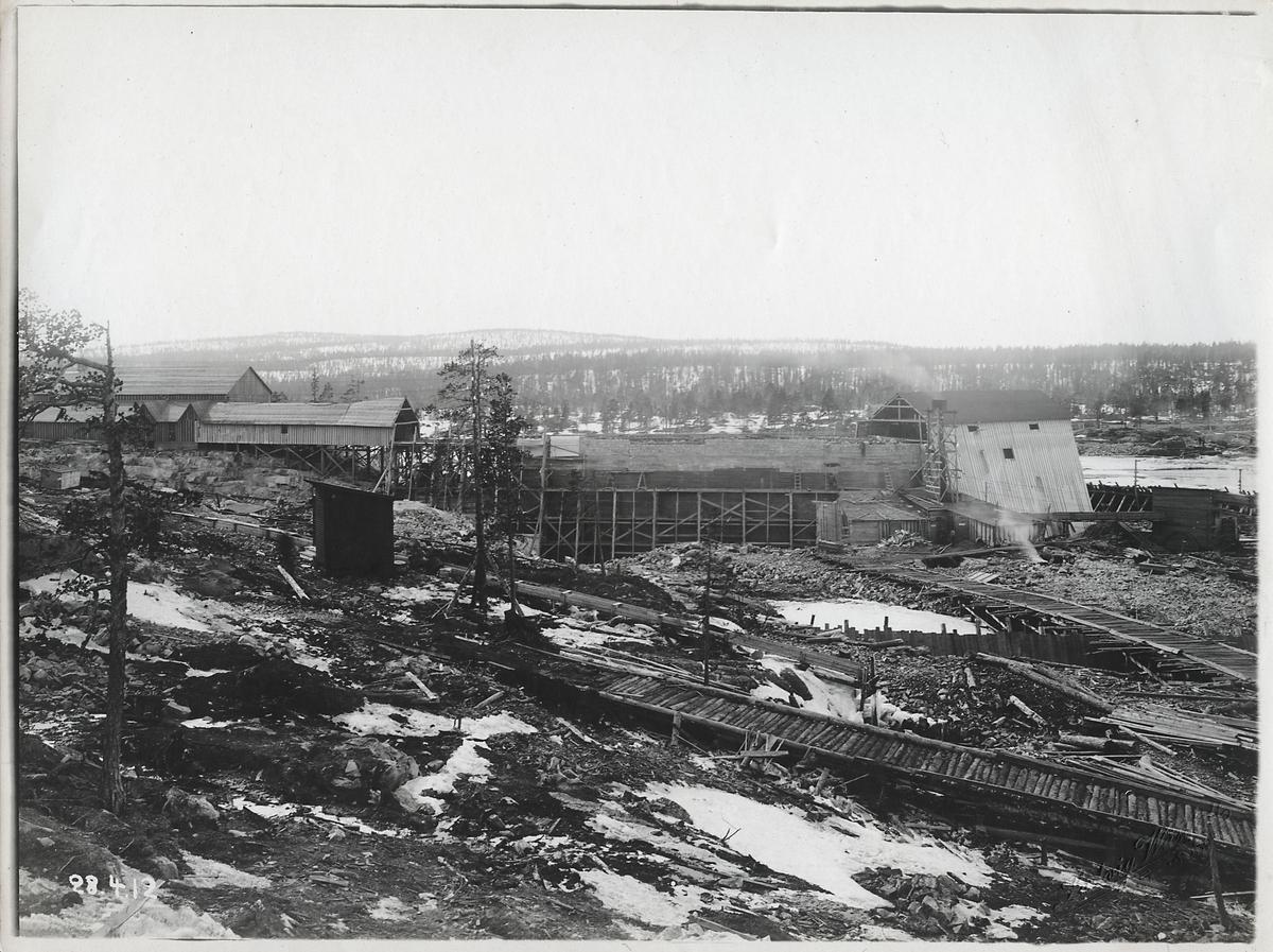 Porjus kraftverk under byggnation vid Stora Lule älv. Varmhuset, fångdammar på ön samt provisorisk bro för transport av virke.