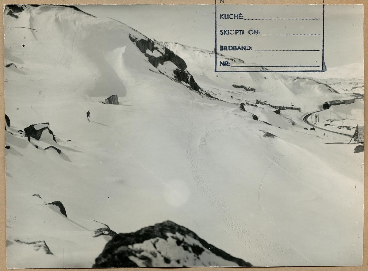 Fotografi taget i Björnefjeld vid Riksgränsen. På fotot finns också en man på skidor samt snöskärmar och snögalleri.