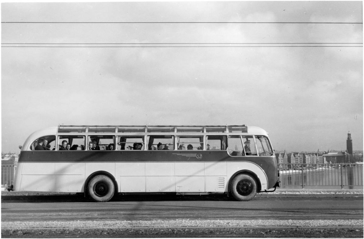 Statens Järnvägar, SJ buss 1102-T på Västerbron med Stockholms Stadshus i bakgrunden.