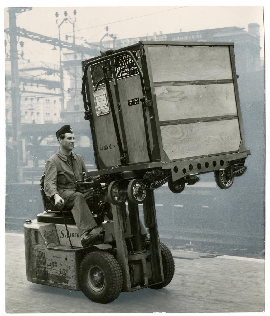 Truck lastad med småbehållare.