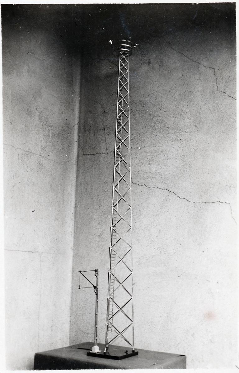 Modell av ett belysningstorn och en kontaktledningsstolpe.