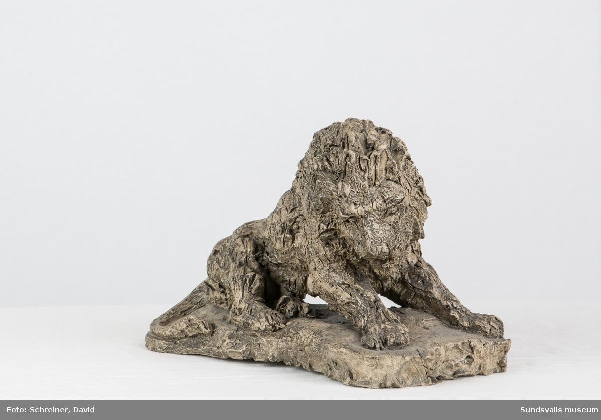 En patinerad gips skulptur i from av ett gammalt lejon med kraftig man.