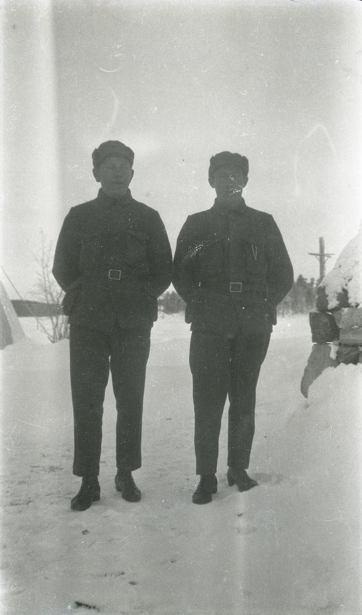 Portrett av to soldater stående utendørs.
