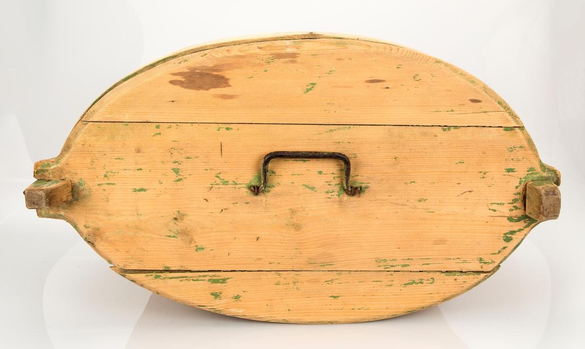 Oval, sveipet og sydd tine. Rester av grønn maling noen steder, hovedsaklig på detaljer. Jernhåndtak på lokket, jernforsterkning i bunnen.