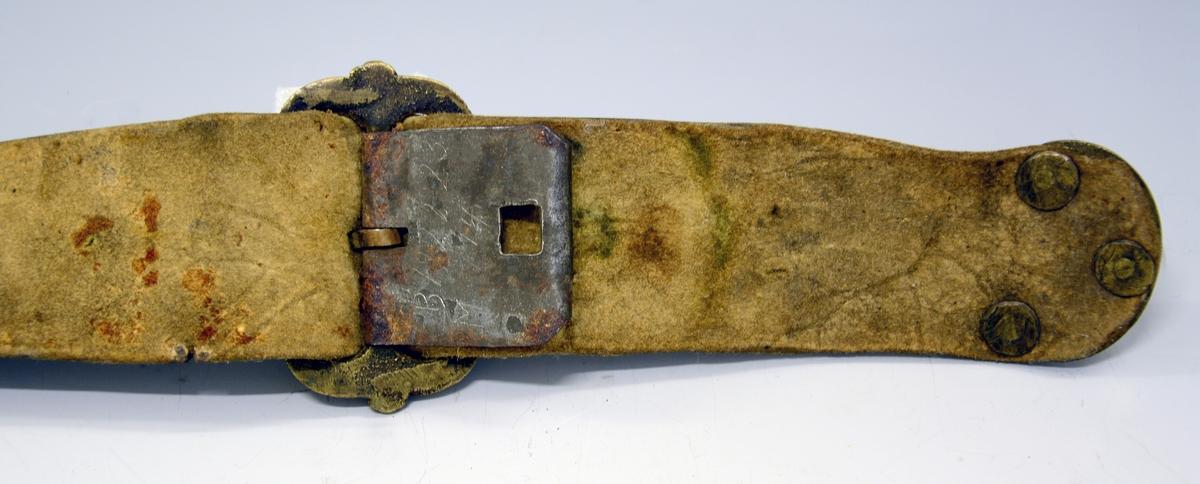 Tvislire med belte. Fra protokollen: Tvislir med belte. Sliri av vatnbarka lêr med slirejarn i vanlegt mot. Sliri er ornera med pressa band i strikmynster; paa den eine fyribokstavane: OASEH, paa den andre sliri aarstalet 1735. Beltet er av semska skinn med stolar av støypt massing. Sproten (hempa) er nyrelaga med graven rank; sylgja (spenna) er avlangrund, med langsidune moddelera i rundmaga bursstolpar med rankornament paa. Sliri er fest i beltet med eit slirehengsle, like eins av semska skinn i dubbeltlagd reim. Paa denne er 4 sylgjur, kvar med 2 ringur i, og millom kvar sylgje ein smøygjestol, i alt 3. Desse er smøygde yvi baae reimlegg, og platemynsteret uppaa er dana av 4 nyrehjarto i firkant, mest som paa rosesylgja. Ornamentiken baade her og paa sylgjune er millomaldersk. Knivane vantar (mangler). (R.Berge)