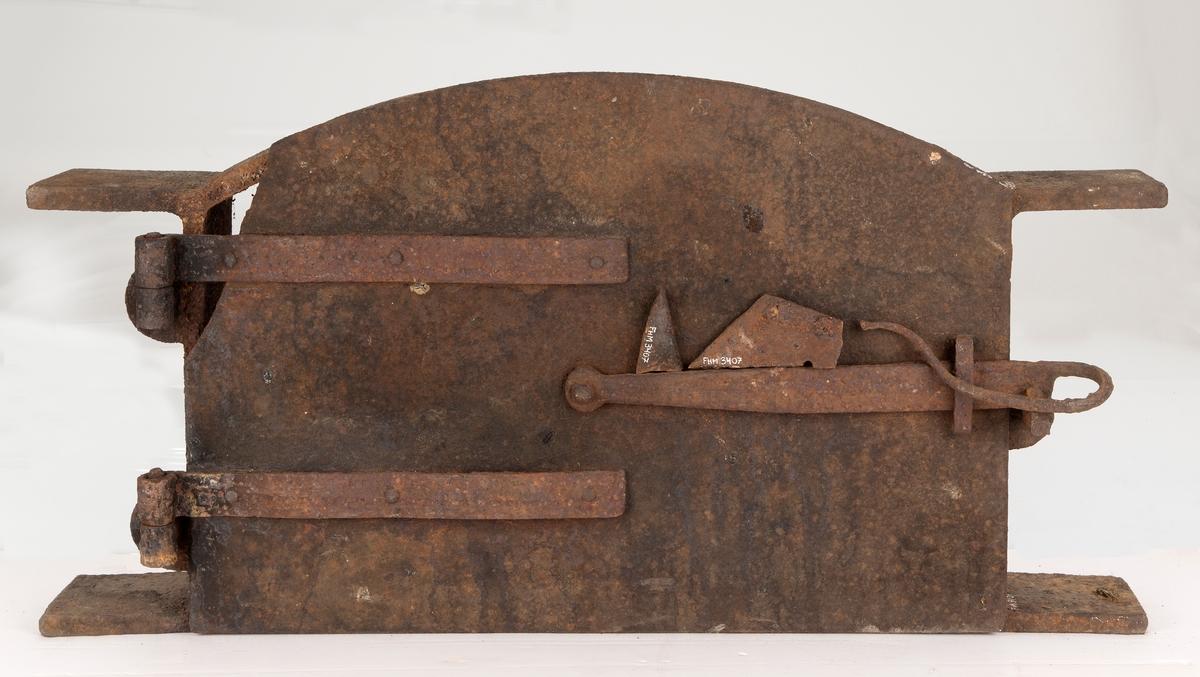 Støpejernsdør med innmuringsramme til bakerovn. Rektangulær, buet øverst. To hengsler og lukker. Øverst i dørens venstre hjørne mangler en 13,5 cm lang bit. Delen er tatt vare på, men er brukket i to.