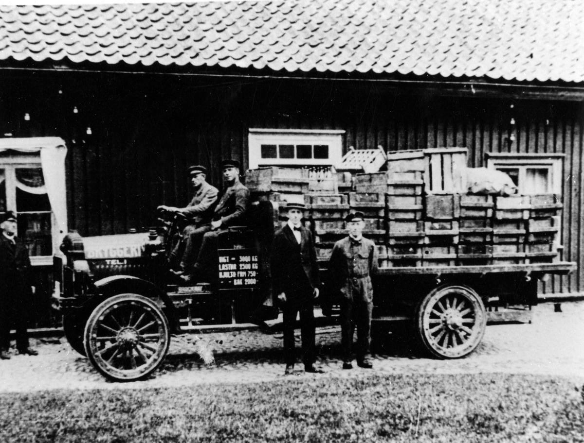 På Alingsås bryggeris gård är företagets lastbil fotograferad, troligen i samband med bilens leverans 1 maj 1921. Lastbilen är av det engelska fabrikatet Brockway och har massiva hjul, 4 cylindrig motor, kardandrift, gaslyktor och avlastad bakaxel. Männen porträtterade vid bilen är, från vänster, Hjalmar Möller, Gunnar Frödeberg, Herr Odqvist, Ivar Karlsson och Sten Möller.