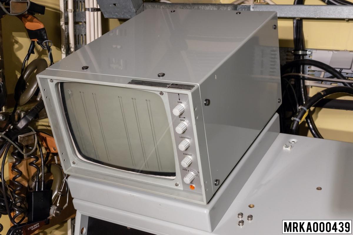 TV-kamrean på MST 727 Sensor-kärra används tillsammans med lasern för optisk spaning och målföljning samt för nedslagsobservationer när siktförhållandena så medger. TV-indikatorn visar den bild som TV-kameran registrerar. TV-indikatorn sitter överst på målföljare A panel.  Ursprungsbeteckning: PHIL-RP 6570218