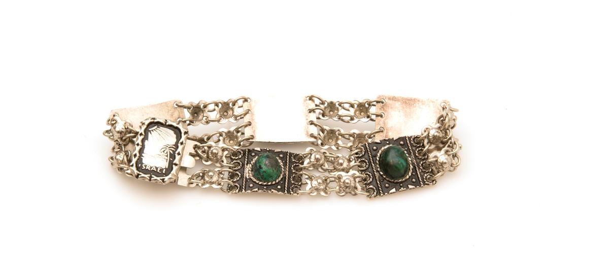 Armband av sterlingsilver med fem infattade ovala gröna stenar med inslag av svart. Stenarna är placerade på varsin gjuten, något välvd, platta med små dekorationer. Plattorna är sammanlänkade genom två parallella kedjor mellan varandra. Låset skjuts in under en gjuten platta med mönster av en sol, en palm och texten ISRAEL Låset är även smitt.