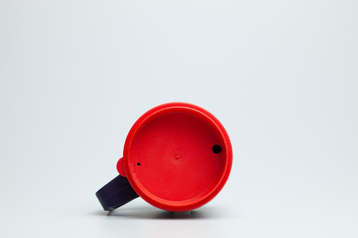 Et lokk i rød hard plast. I lokket er det et lite hull, der man kan drikke kaffe igjennom.