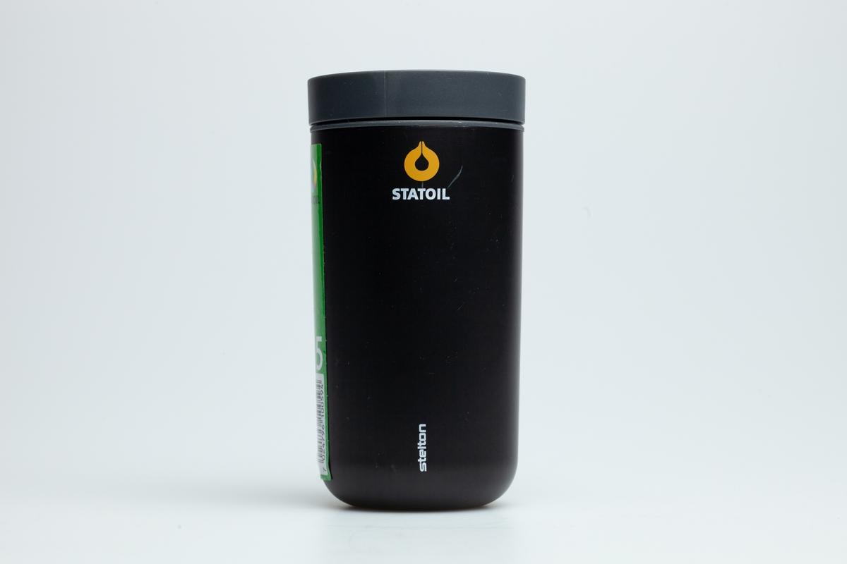 En sort Statoilkopp uten hank. På båndet står det 2016. En rød etikett på koppen er med QR-kode, strekkode, Statoillogo og tallet 16.