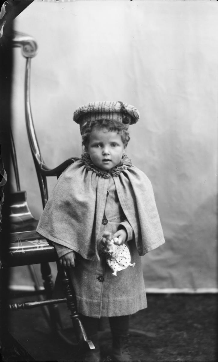 Jente med fine klær og hatt og lita dokke, antatt 4-6 år