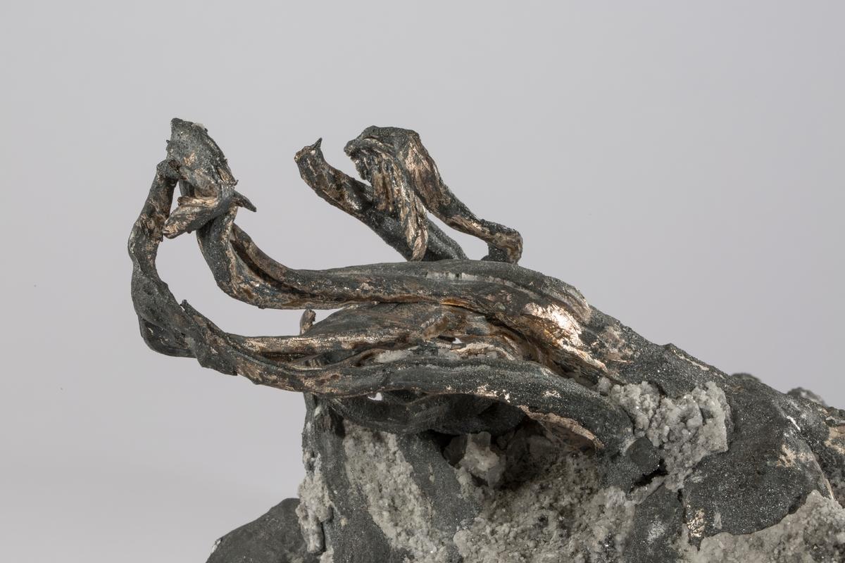 """Etikett i tråd: 9 (rund med metallkant) Vekt: ca. 10286,5 kg Størrelse: 23 x 17 x 15 cm Stuffen ble vist på Verdensutstillingen i New York i 1939 Fra liste over sølvstuffer som ble sendt til Verdensutstillingen:  """" 9. Mildigkeit Gottes 1938, dyp 124 m, vekt 10.44 kg (brutto), 9.80 kg (netto), verdi kr. 2500. Ged. sølv. Stykke av en veggdekorasjon i druserom utstyrt med trådbundter av tvillingkrystaller, delvis overtrukket av svovelkis og sølvglanskrystaller.""""  BVM 3143 har falt av denne stuffen"""