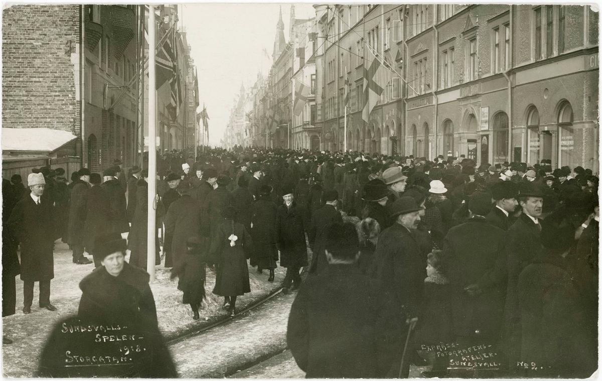 Folkvimmel efter Storgatan under Sundsvallsspelen 1918. Vykort.