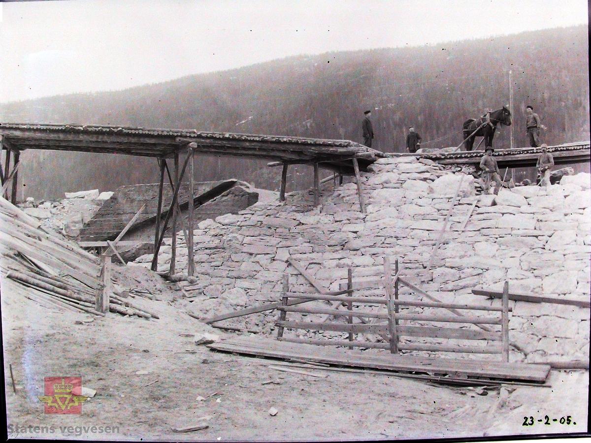 Gamle Gulsvik hengebru under bygging 1905. Brua har en  total lengde på 97 meter. Bygd i perioden 1903-1906 av Kværner Brug i Oslo. Inngikk som del av Hallingdalvegen fram til 1971 da vegen ble lagt om og ny bru bygd ved siden av. Da den ble bygd var dette Skandinavias lengste hengebru. Den er et tidlig eksempel på hengebru i Norge og er derfor tatt med i Nasjonal verneplan for veger, bruer og vegrelaterte kulturminner. Fredet ett § 22a i kulturminneloven i 2008. Rehabilitert med utskifting av tredekke og maling av stålkonstruksjoner i 2010.  På bildet ser vi steinfyllingen bak vestre brukar. Steinen blir kjørt fram med hester fra jernbaneanlegget. Til venstre ser man noe av forankringsklossen.