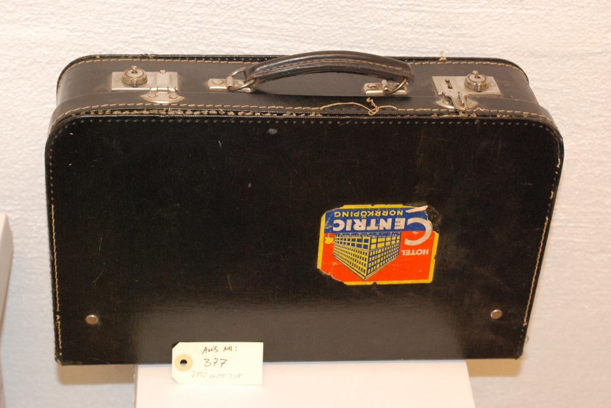 Sort skinnimitert koffert påsatt a) 1 klistremerke fra Hotel Centric i Norrköping, Sverige og b) 2 klistremerker som gjelder hjemreisen tilbake til Norge i 1945. Kofferten ble benytet under flukt til Sverige i 1942.