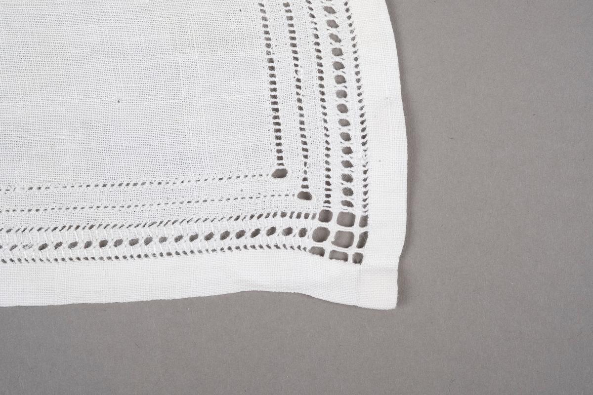 Smalt rektangulert tøystykke brodert med hvit hullsøm på tre sider.