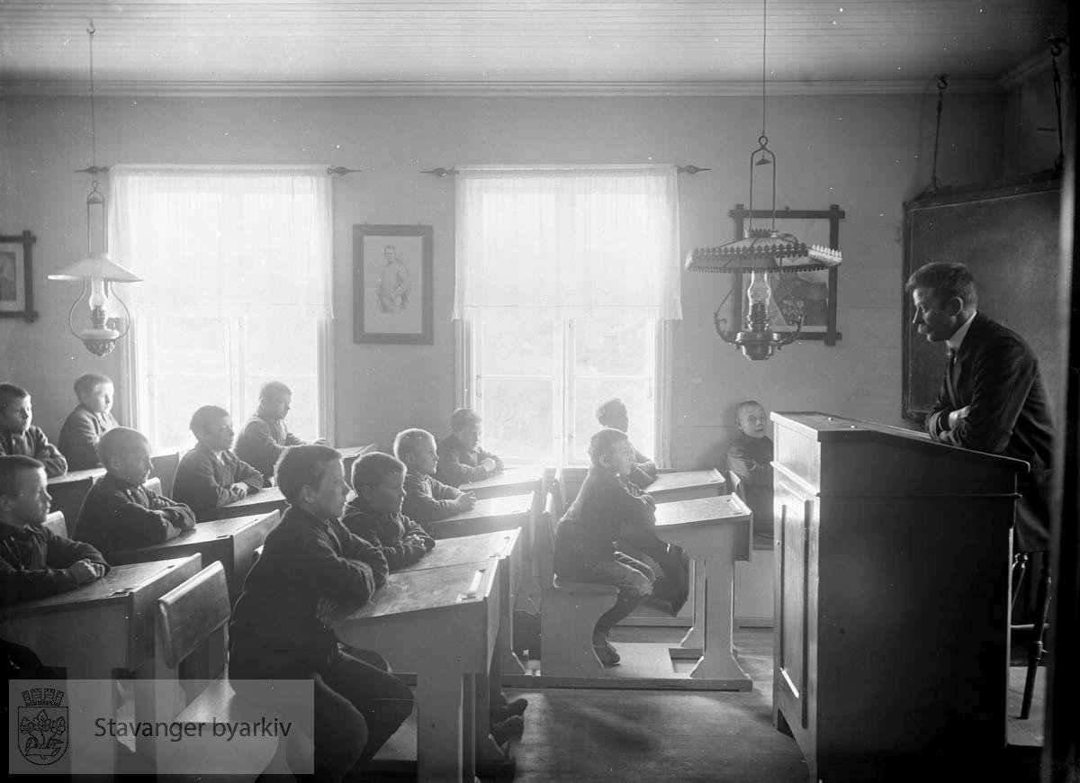 Elever ved pultene, lærer underviser.