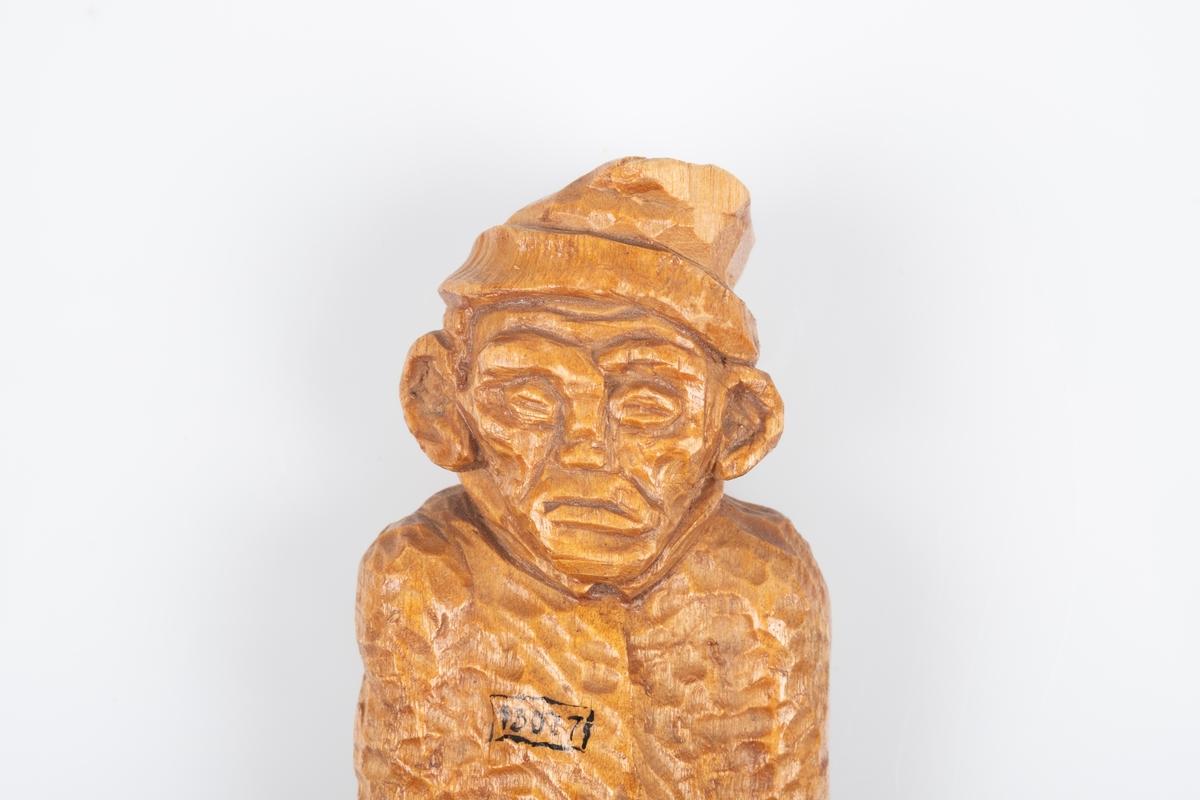 Utskåret trefigur som forestiller en mannlig fange med fangedrakt. Han står med hendene i bukselommene. På brystet er fangenummeret hans. På baksiden av skoen er en inngravert signatur.